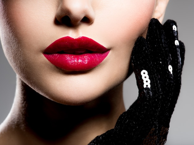 Сlose-up women's lips with red lipstick and black gloves on cheek