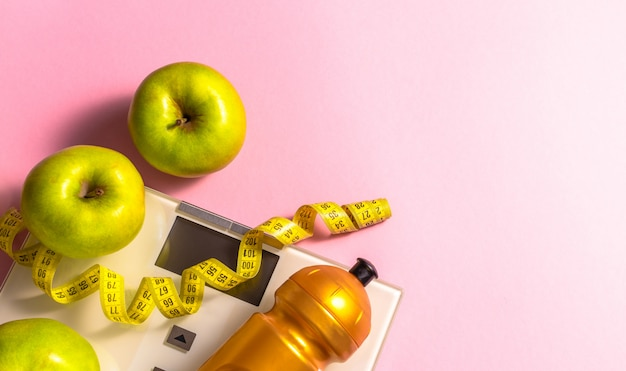 Lose weight concept with scales, measure tape, gym water bottle and green apples on pink background.