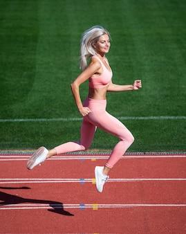 Худеть. скорость и энергия. выносливость. сексуальный бегун в фитнес-спортивной одежде. спринт на ипподроме на открытой арене. тренировки и тренировки. спортивный женский тренер работает. женщина спортивный тренер в движении.