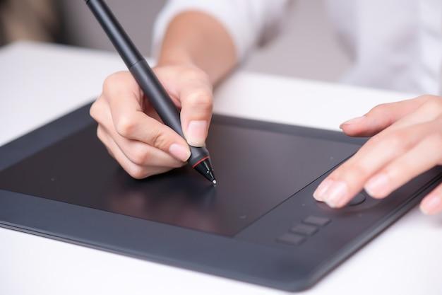 Loseup женского портниха зарисовок и рисунков с графическим планшетом. горизонтальная форма, вид сбоку