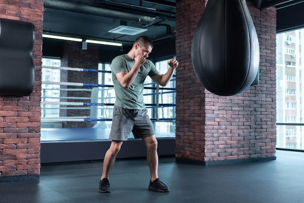 Losing competition. dark-haired professional boxer feeling some anger while training after losing competition