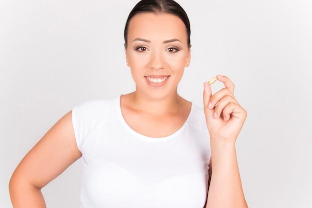 減量とダイエットの概念。美容トリートメントコラーゲン食品サプリメント。カプセルを保持しているプラスサイズの女性。