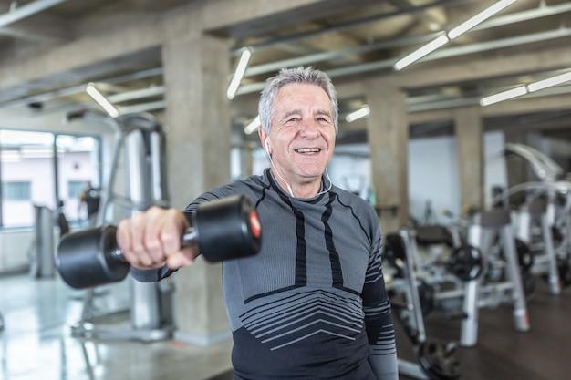 피트니스 센터에서 노인이 수행하는 덤벨 훈련으로 체중을 줄이고 힘을 얻습니다.