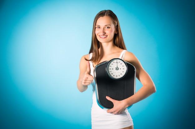 体重を減らす、体重計を持つ若い女性
