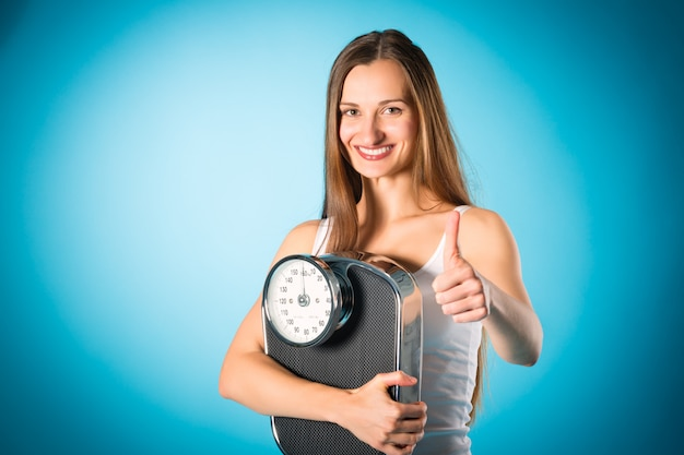 Losing weight, young woman with measuring scale