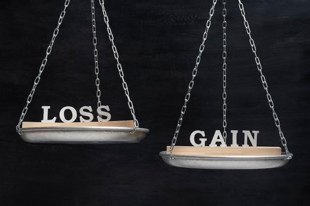 Понятие баланса убытков и прибыли. весы на черном фоне