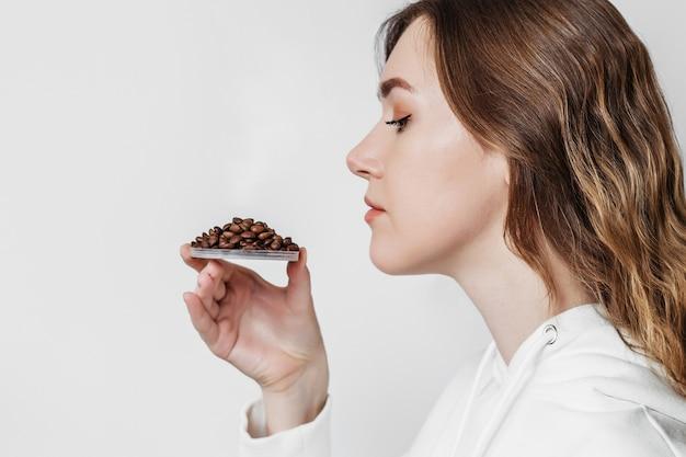 Потеря запаха. закройте вверх по портрету кавказской молодой женщины нюхая изолированные кофейные зерна. вид сбоку. скопируйте пространство. концепция коронавируса