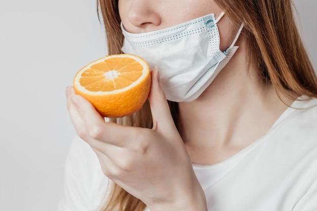嗅覚喪失の概念。オレンジを嗅ぐ医療マスクの白人の若い女性