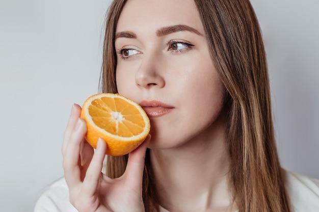 Концепция потери запаха. крупным планом портрет кавказской молодой женщины, держащей апельсин возле ее носа, изолированные