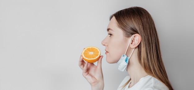 嗅覚喪失の長いバナー。オレンジを嗅ぐ医療マスクを着た白人の若い女性。プロフィールビュー