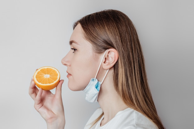Loss of smell concept. caucasian young woman in a medical mask sniffing an orange. profile view