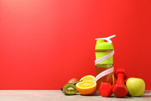 Аксессуары для похудения на сером столе на красном фоне