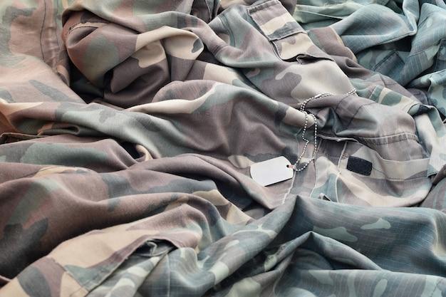 Потерянный и пустой армейский жетон, лежащий на куче сложенной камуфляжной одежды