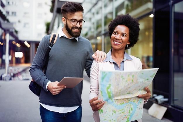 지도를 들고 도시에서 잃어버린 행복 한 커플. 여행, 관광, 사람 개념
