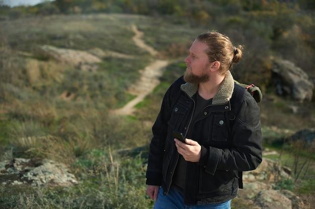 초원에서 길을 찾는 스마트 폰으로 길을 잃은 등산객. 자연을 여행하고 가제트를 사용하는 사람들의 개념