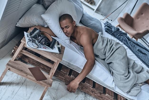 깊은 잠에 빠졌습니다. 집에서 침대에 누워있는 동안 잠자는 젊은 아프리카 남자의 상위 뷰