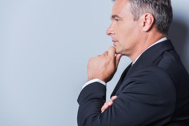 Погружен в деловые мысли. вид сбоку вдумчивого зрелого мужчины в формальной одежде, держащего руку за подбородок и смотрящего в сторону, стоя на сером фоне