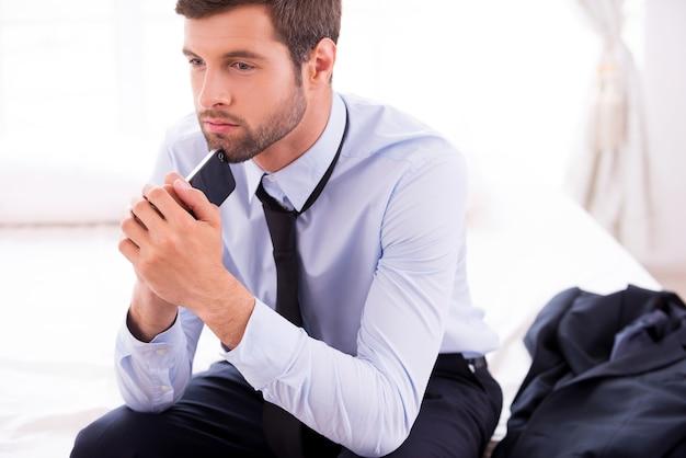비즈니스 생각에 빠졌습니다. 셔츠와 넥타이를 입은 사려깊은 청년은 휴대전화로 턱을 만지고 침대에 앉아 멀리 바라보고 있다