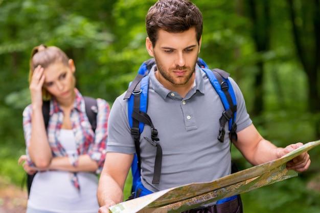 숲에서 길을 잃었다. 배낭을 메고 지도를 살펴보는 사려 깊은 청년