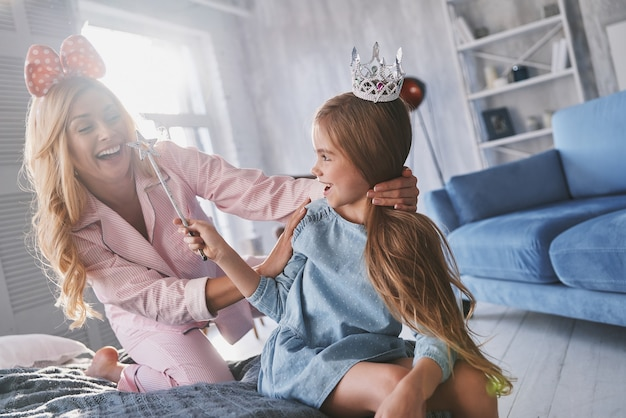 Затерянный в своей сказке. красивая молодая мать смотрит на свою милую дочь и улыбается, сидя на кровати у себя дома