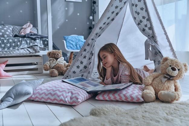 Затерянный в своей сказке. милая маленькая девочка, читающая книгу