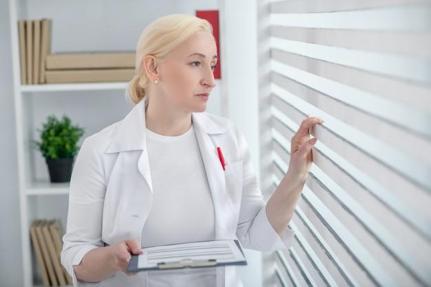 思考を失った。窓の近くに立っている彼女の手にフォルダーを持つ白衣のブロンドの髪を持つ女性。