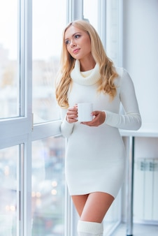 생각에 빠졌다. 따뜻한 스웨터와 양말을 신고 커피를 마시고 집에서 창문을 통해 바라보는 아름다운 젊은 여성