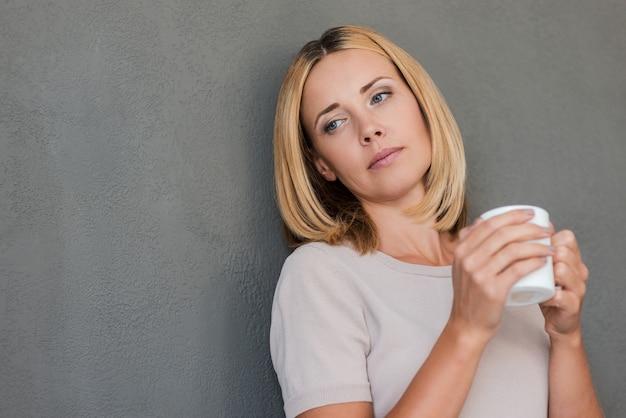 考えを失った。壁に寄りかかってコーヒーを保持している物思いにふける成熟した女性