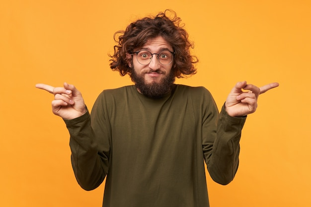 Lost in making choice, curly-hair bearded man in glasses pointing his index fingers on both sides