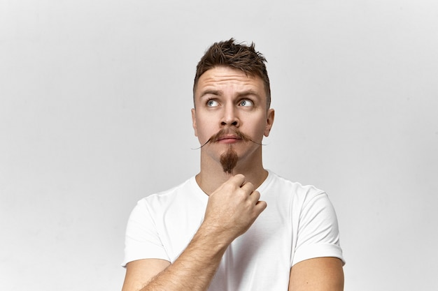 Lost in thoughts. isolated studio view of attractive stylish young european male hipster with goatee and msutache looking up, having impatient nervous facial expression, waiting for something