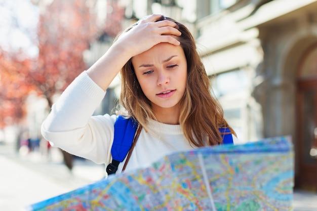 여행에서 도시 지도를 보고 길을 잃은 관광객. 방향을 찾고 있습니다.