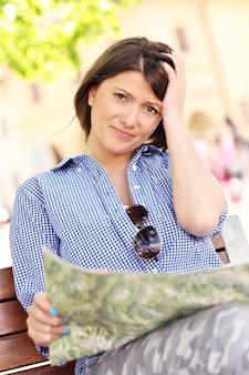 ベンチに座っている地図で失われた観光客