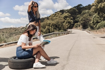 Lost woman sitting on tire with her friend looking at map