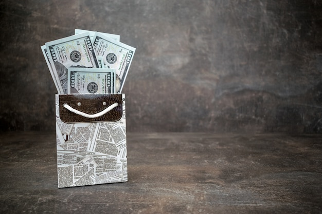 A lot of 100 dollar bills in black white gift bag on dark background
