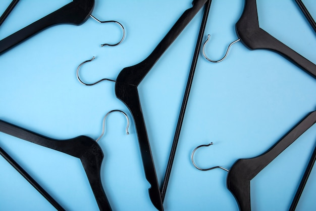 A lot of black clothes hangers on blue background