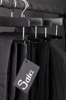 A lot of black pants jeans and jacket hanging on clothes rack