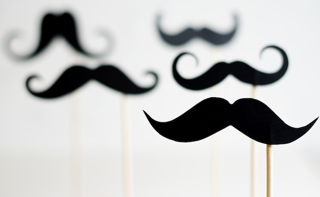 A lot of black paper moustaches on sticks