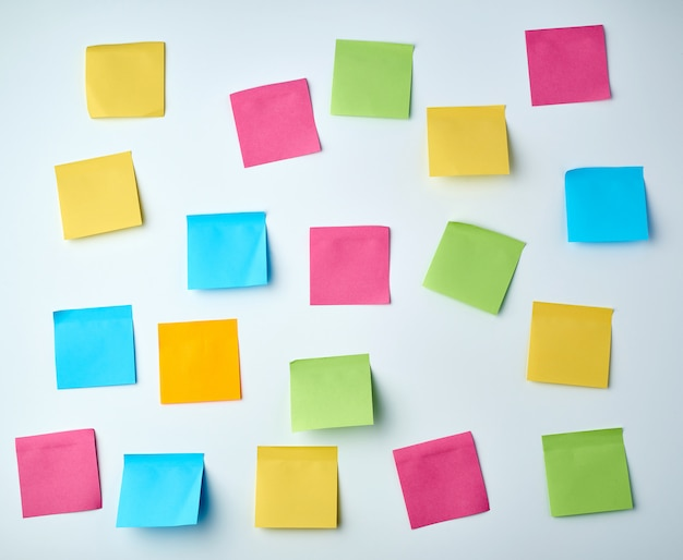 Lot of blank square paper multicolored stickers on a white wall