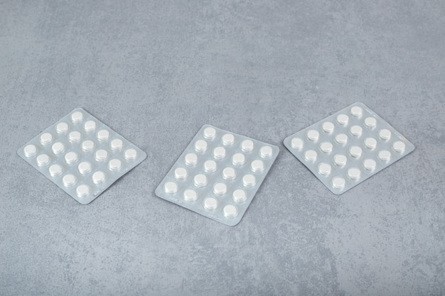 Molte vesciche con pillole bianche su superficie grigia