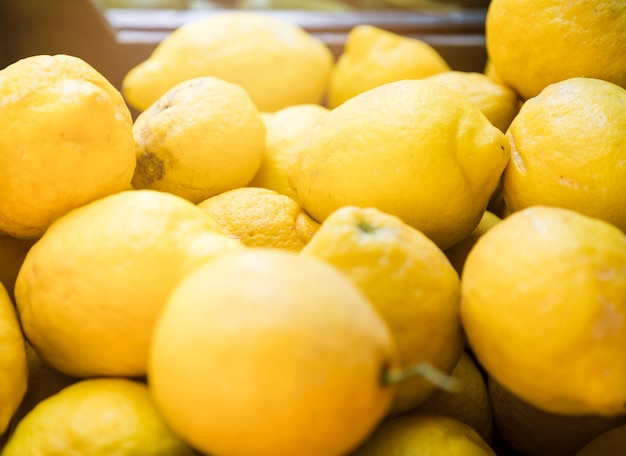 Lot of bright yellow lemons in supermarket