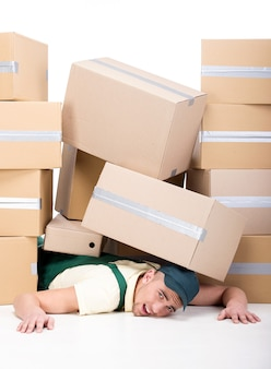 A lot of cardboard boxes fell on a young man.