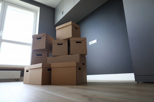 Lot of cardboard boxes on wooden floor new flat closeup