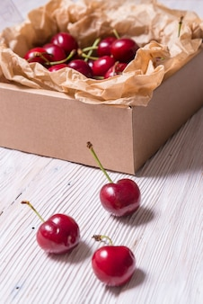 Lot of cherry in kraft cardboard box on wooden table