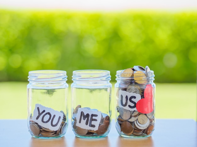 A lot coins in glass money jar on the wood table. saving for family concept
