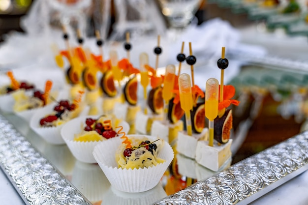 Lot of cold snacks on buffet table. sweet appetizers. catering at celebration.