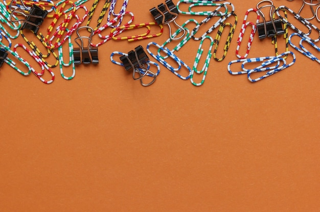 Lot of colored paper clips on brown background. minimalistic office concept. copy space
