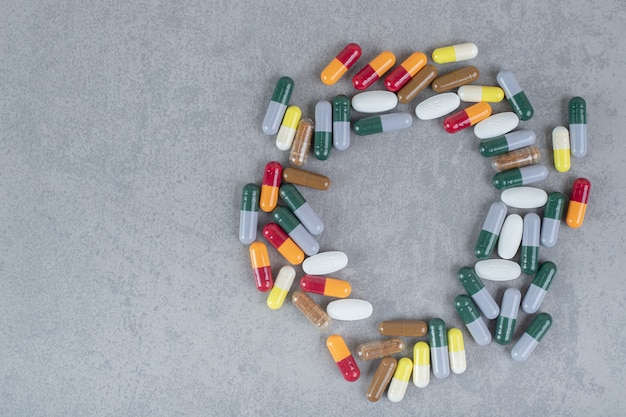 A lot of colorful mixed pills on a gray surface