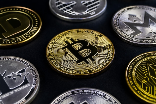 A lot of cryptocurrency coins lie on a dark surface
