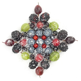 Lot of different berries in the shape of a square on a white background. healthy fresh vegetables and food