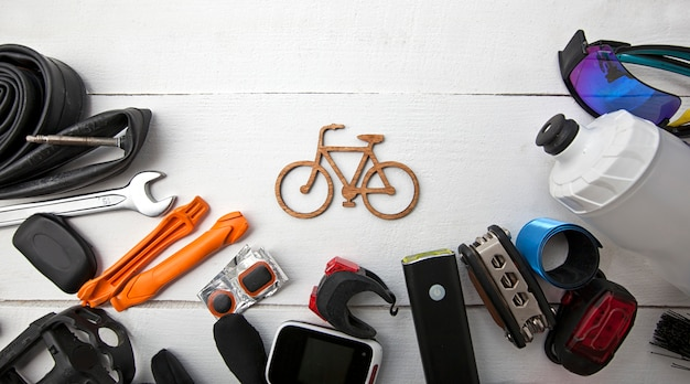 A lot of different bicycle accessories lying on wooden table around a little bicycle icon
